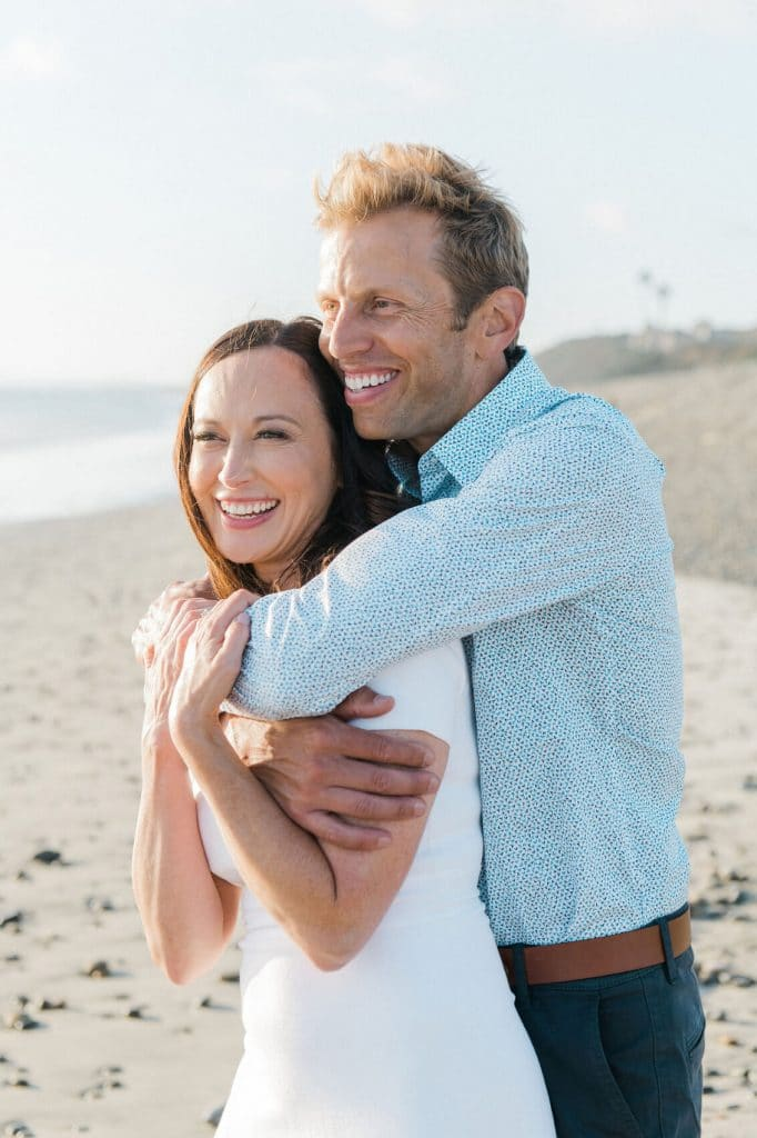 couple embracing on sand during ponto beach engagement photo shoot