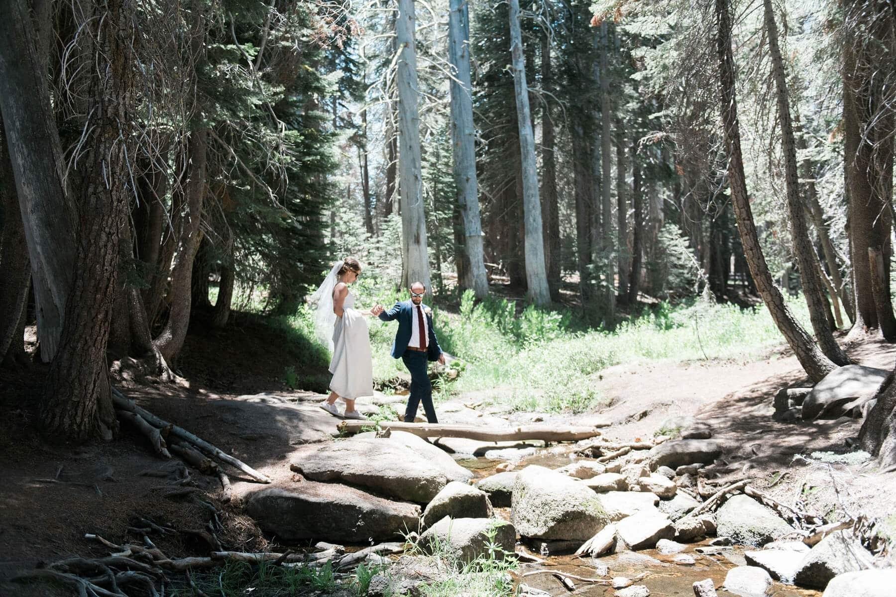 groom holding bride's hand as she walks over creek during yosemite adventure elopement