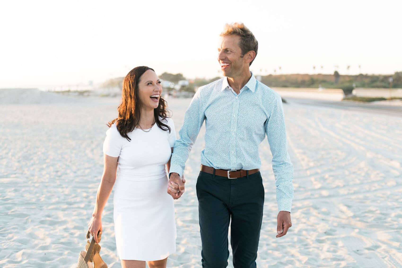 couple holding hands walking on beach laughing at sunset ponto beach carlsbad