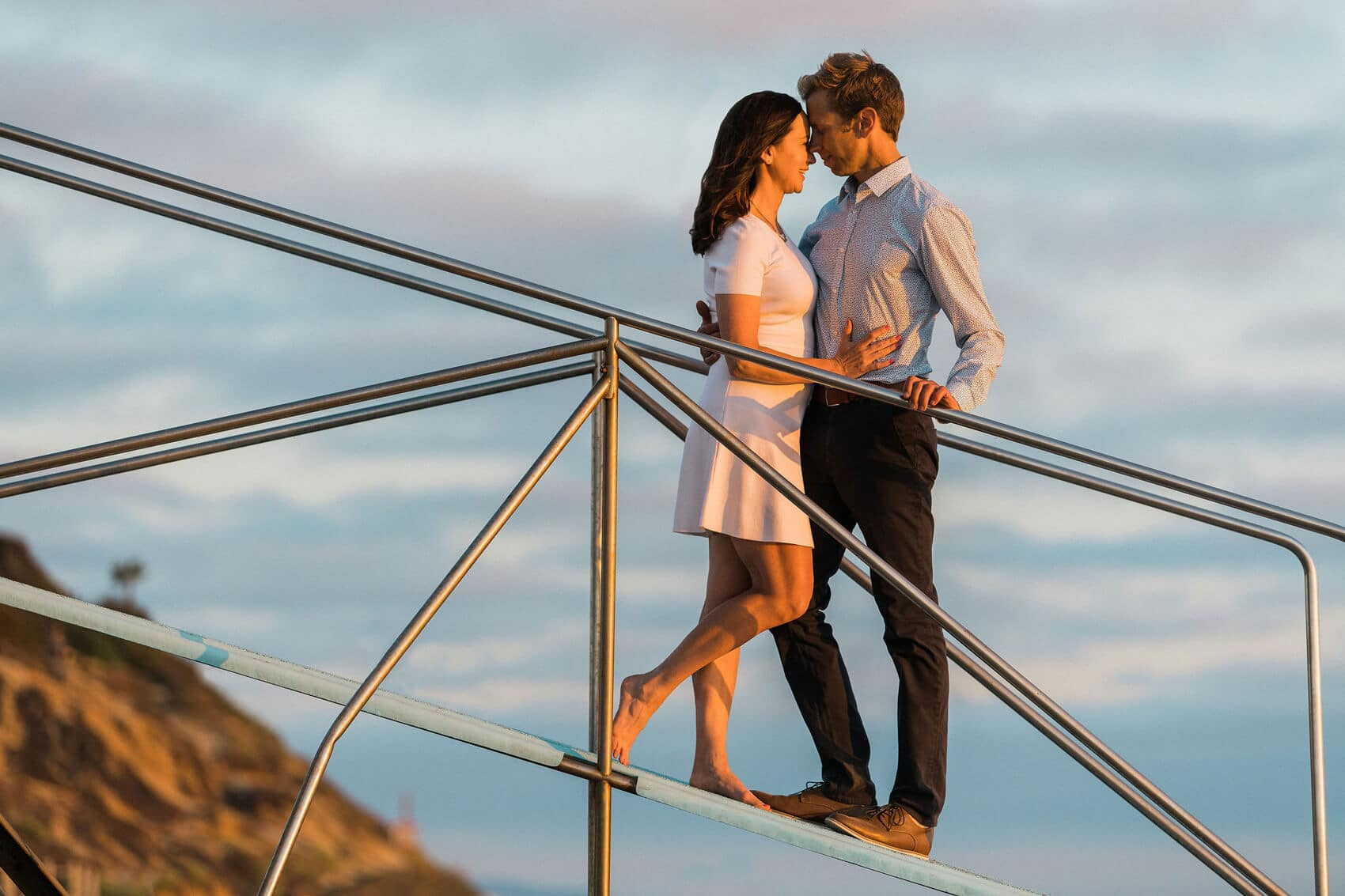 couple embracing on railing of lifeguard tower at sunset in carlsbad