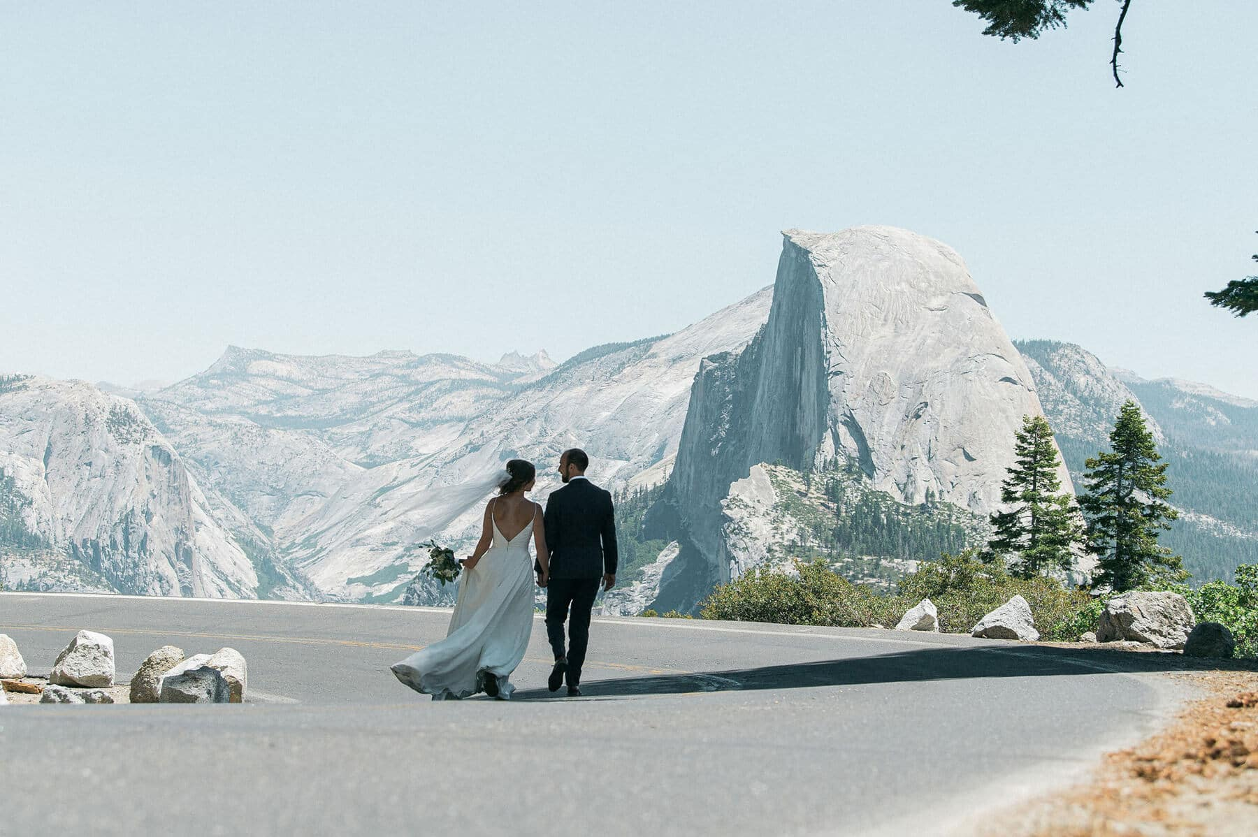 bride and groom walking on road to glacier point with halfdome in background yosemite adventure elopement