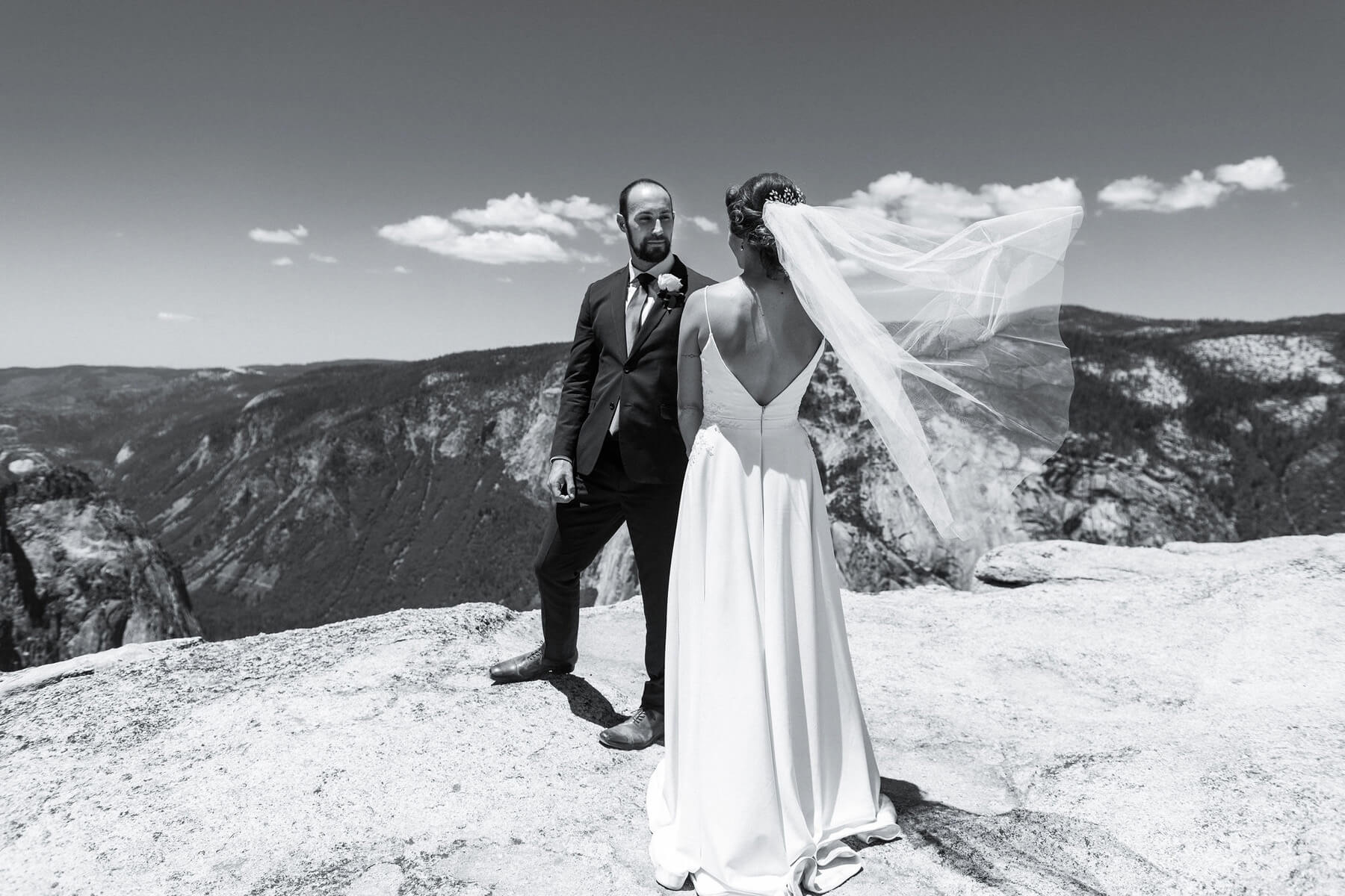 groom looking at bride with veil swirling in wind taft point elopement