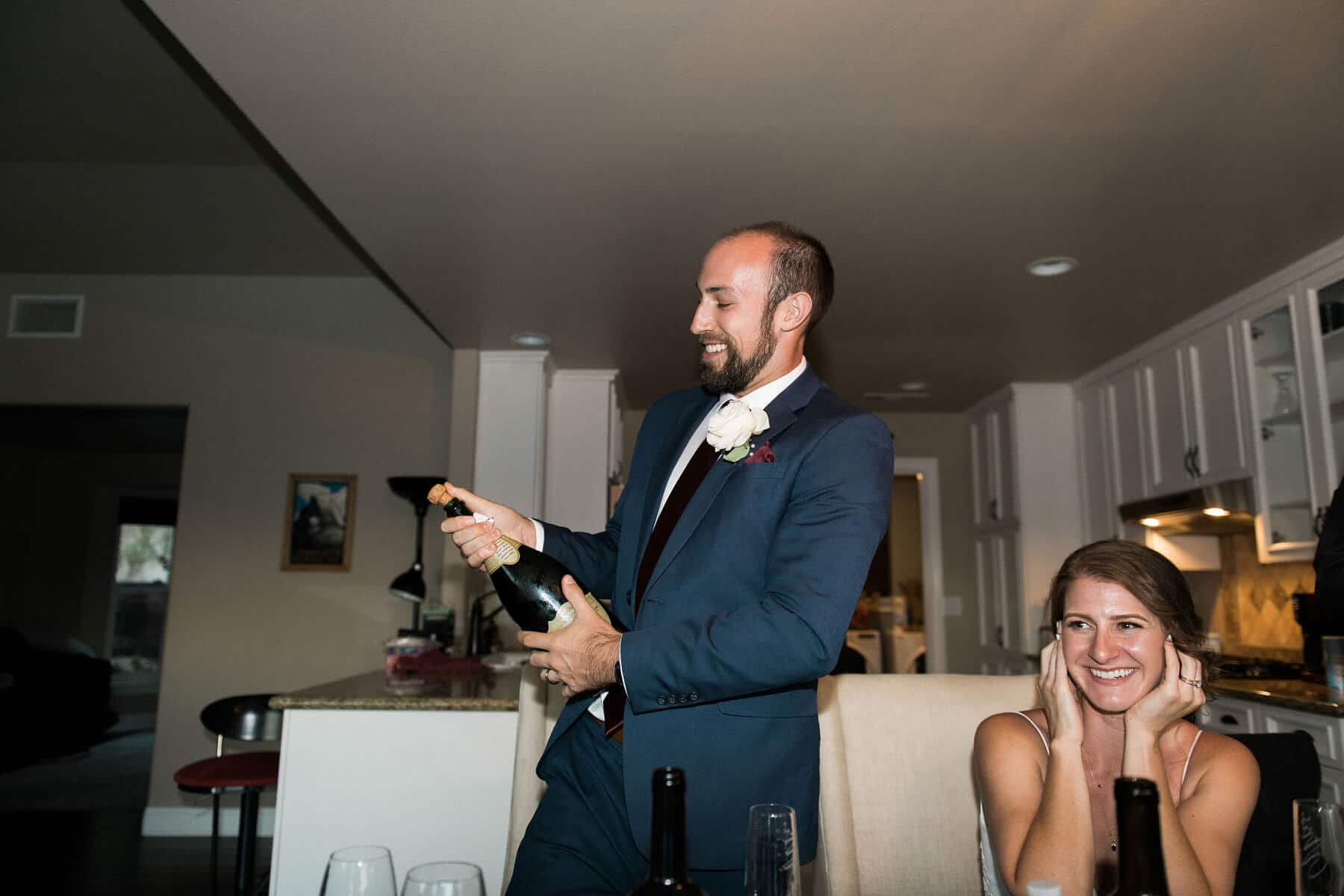 groom popping bottle of champagne while bride smiles and covers ears