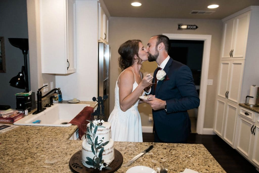 bride and groom kissing after cutting cake at intimate wedding reception at private residence in oakhurst california