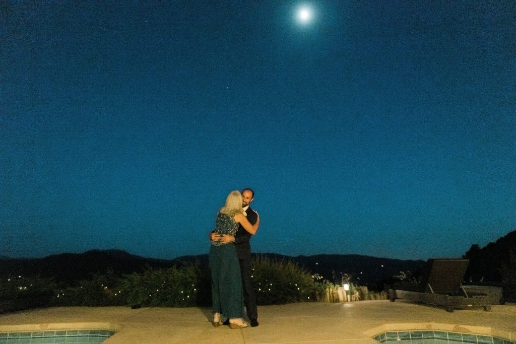 mother and son dancing under moonlight during intimate reception in oakhurst