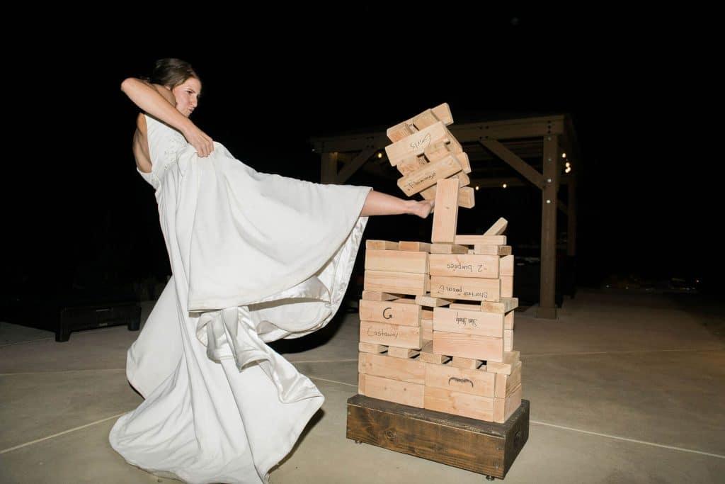 bride kicks over a life-sized jenga game intimate wedding reception oakhurst