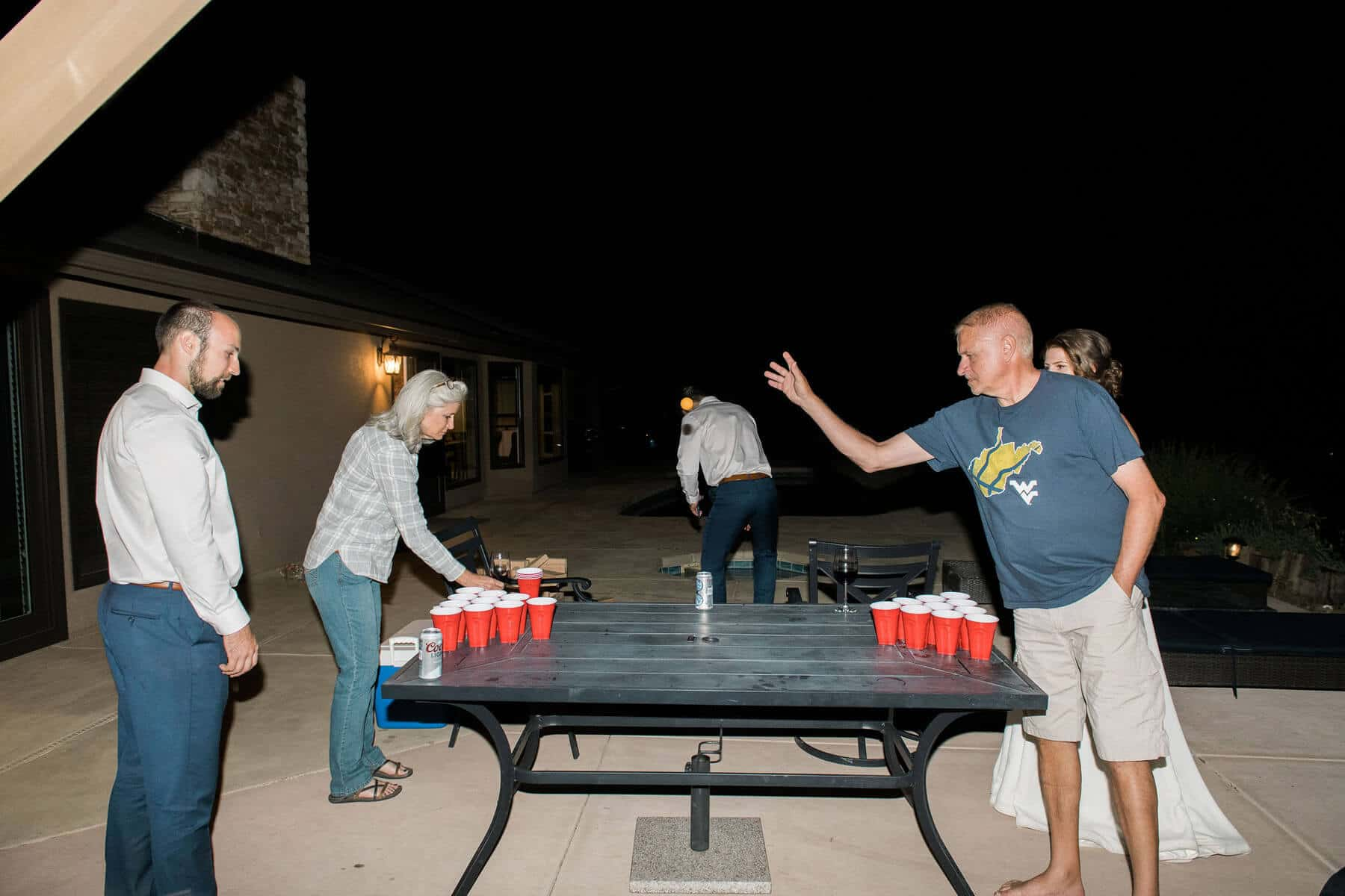 bride and groom and family play beer pong on patio of private residence during intimate wedding reception oakhurst