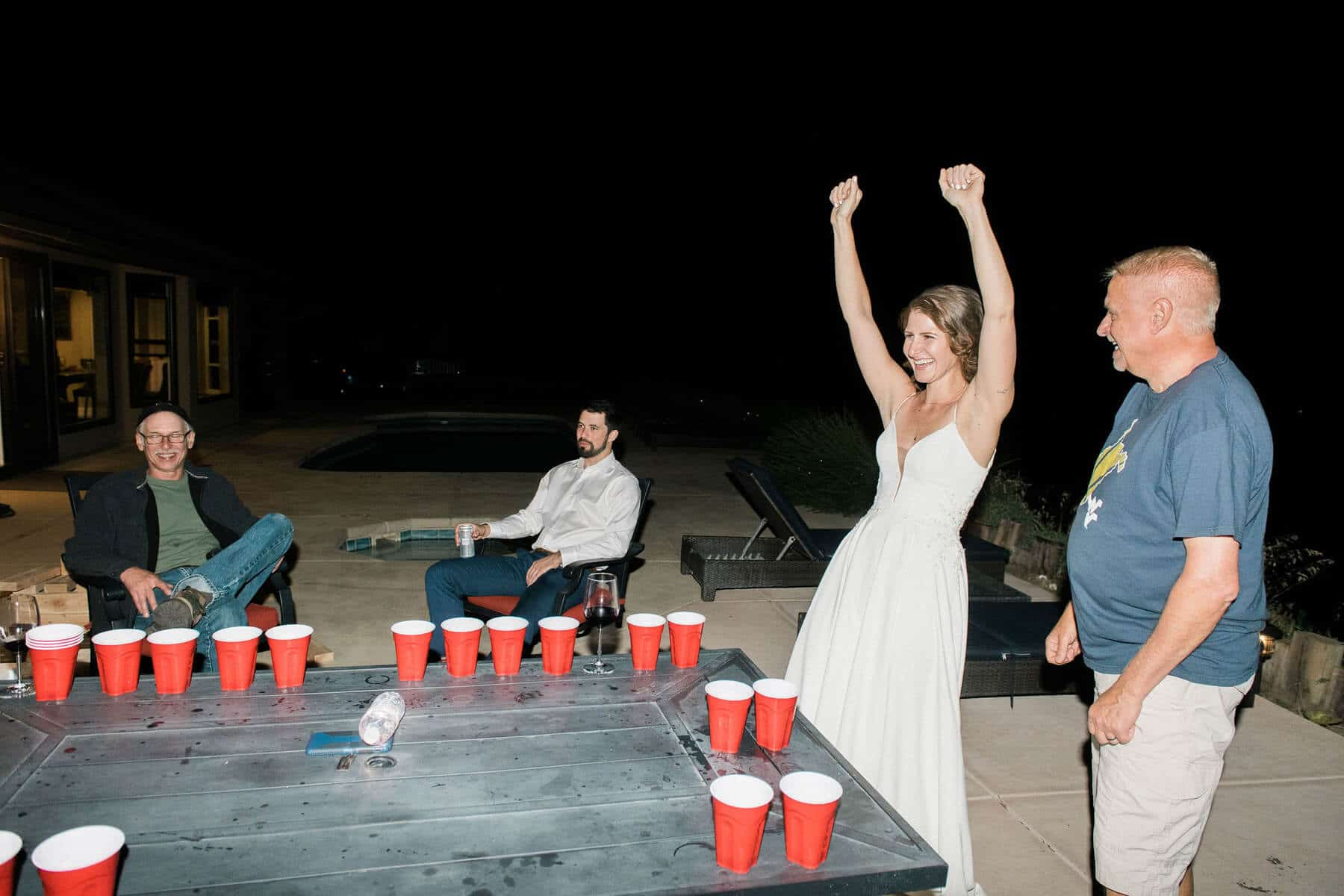 bride and father react to winning game of beer pong
